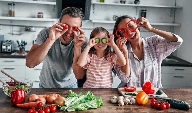 Mamma, papà e figlia stanno cucinando in cucina. concetto di famiglia felice. l'uomo bello, la giovane donna attraente e la loro piccola figlia sveglia stanno facendo l'insalata insieme. uno stile di vita sano.