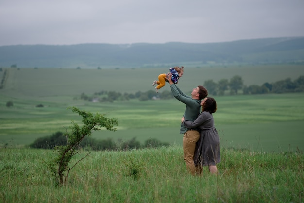 Mamma, papà e figlia. il padre lancia sua figlia nel cielo. la mamma abbraccia il papà da dietro.