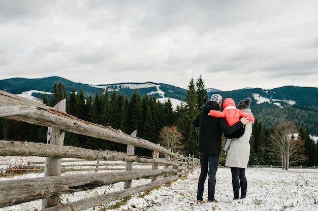 Mamma, papà, ragazza cammina in montagna, guarda la natura. figlia di padre, madre e figli che gode del viaggio.