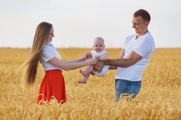 Mamma e papà che tengono bambino carino all'aperto. giovane famiglia nel campo di grano.