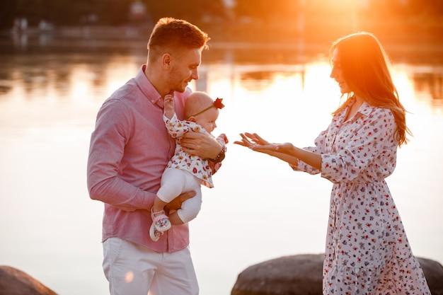 Mamma, papà che abbraccia la figlia vicino al lago sul tramonto. il concetto di vacanza estiva. festa della mamma, del papà, del bambino. famiglia trascorrere del tempo insieme sulla natura. aspetto familiare. messa a fuoco selettiva