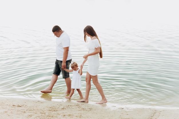 Mamma, papà che abbraccia la figlia che cammina sulla spiaggia vicino al lago. il concetto di vacanza estiva. festa della mamma, del papà, del bambino. famiglia trascorrere del tempo insieme sulla natura. aspetto familiare. luce del sole.