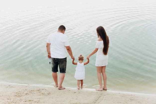 Mamma, papà che abbraccia la figlia che cammina sulla spiaggia vicino al lago. il concetto di vacanza estiva. festa della mamma, del papà, del bambino. famiglia trascorrere del tempo insieme sulla natura. aspetto familiare