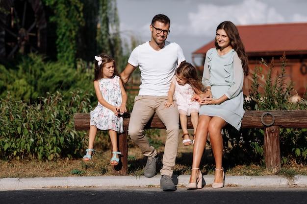 Mamma, papà che abbraccia le figlie si divertono a stare seduti all'aperto e guardare la natura. giovane famiglia trascorrere del tempo insieme in vacanza, all'aperto. festa della mamma, del papà, del bambino.
