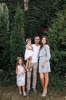 Mamma e papà che abbracciano le figlie amano passeggiare all'aperto e guardare la natura. giovane famiglia trascorrere del tempo insieme in vacanza, all'aperto. festa della mamma, del papà, del bambino.