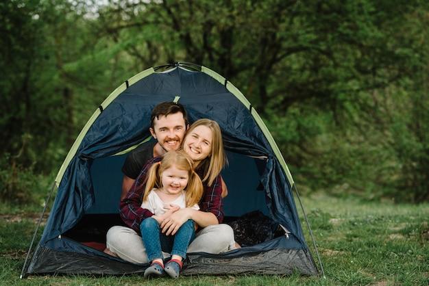 Mamma, papà abbraccia un bambino e si godono una vacanza in campeggio in campagna