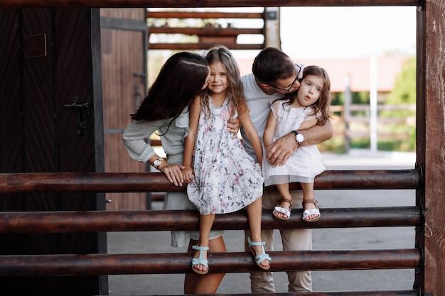 Mamma, papà che bacia le figlie amano camminare all'aperto e guardare la natura. festa della mamma, del papà, del bambino.