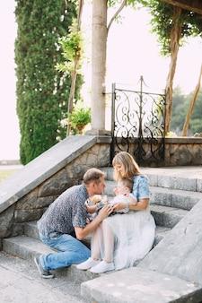 Mamma, papà e figlioletto sono seduti sui gradini della bellissima villa milocer a budva