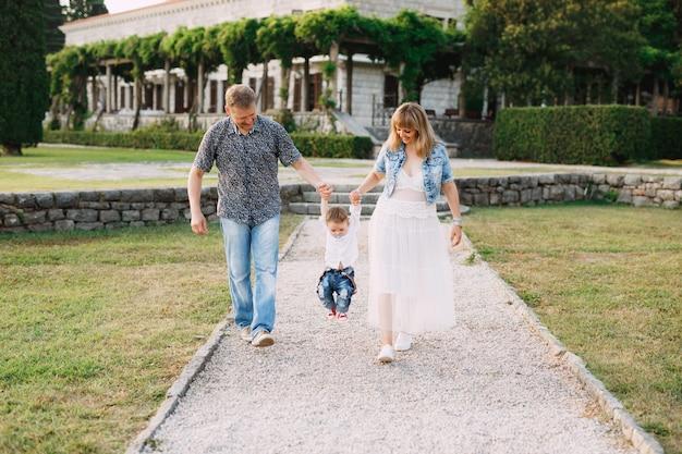 Mamma, papà e figlioletto stanno camminando lungo il sentiero vicino alla bellissima villa milocer, i genitori tengono
