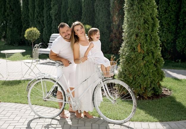 Mamma e papà guidano la loro figlia in un cestino su una bicicletta. vacanze di famiglia. il bambino è felice e ride forte. giro in bicicletta in famiglia.