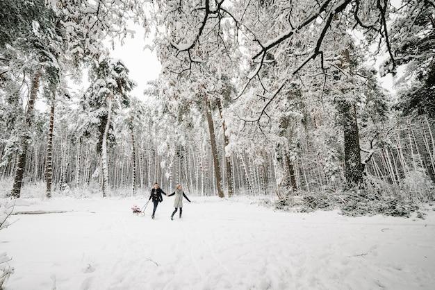 Mamma, papà che corre, figlia in slittino nella foresta invernale.