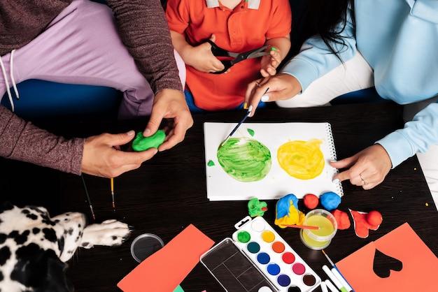 Mamma, papà, figlio e il loro cane giocano con la plastilina e la pittura a casa. concetto di una giovane famiglia caucasica felice