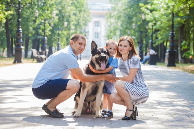 Mamma, papà e figlio a spasso con il loro cane pastore