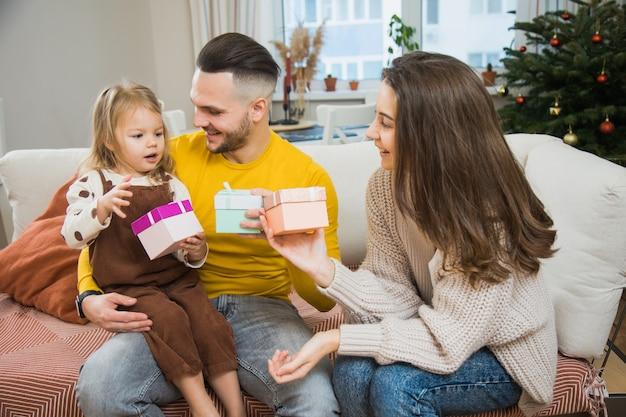 Regalo di unboxing di mamma e papà per la piccola figlia a casa nel periodo natalizio. la famiglia festeggia insieme il nuovo anno.