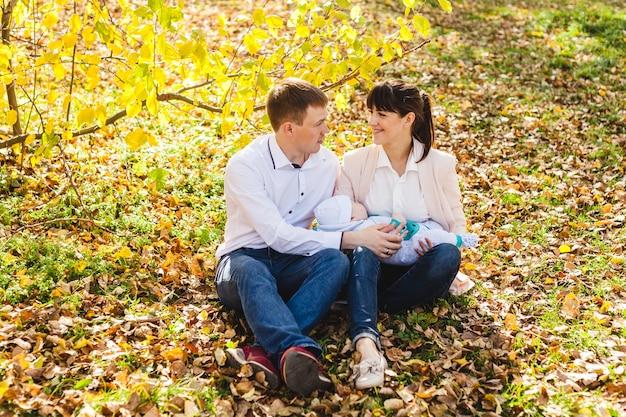 Mamma e papà con un bambino, un ragazzino che cammina in autunno nel parco o nella foresta. foglie gialle, la bellezza della natura. comunicazione tra un bambino e un genitore.