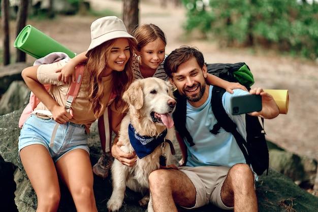 Mamma e papà con la figlia con gli zaini e un cane labrador si fanno un selfie al telefono seduti su una pietra nella foresta. campeggio, viaggi, escursioni.