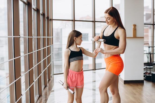 Mamma e figlia stanno facendo esercizi. famiglia in palestra. la bambina con la madre forte si sta allenando con i manubri