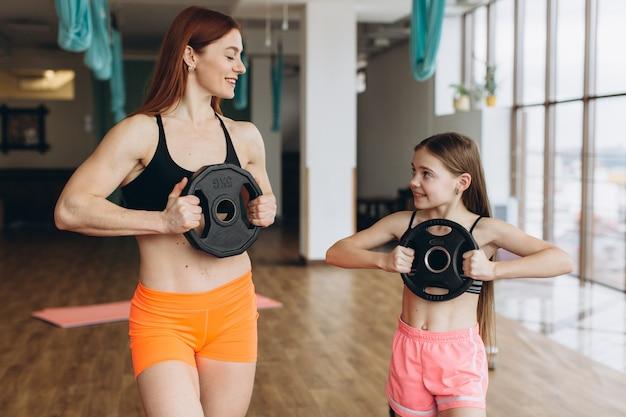Mamma e figlia stanno facendo esercizi. famiglia in palestra. la bambina con la madre forte si sta allenando con le aste di frittelle