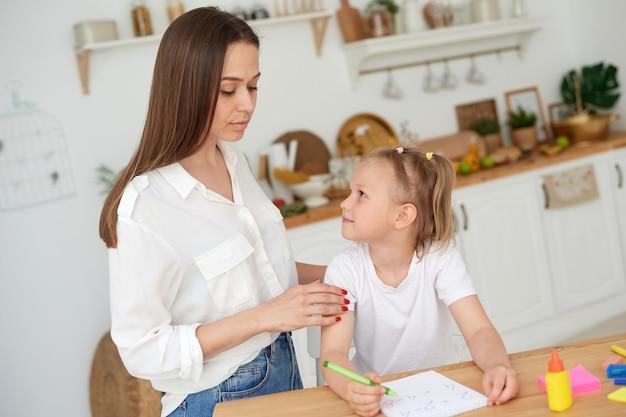 Mamma e figlia stanno facendo i compiti. una bambina completa premurosamente compiti di matematica sotto la supervisione di un tutor. il concetto di prendersi cura di un bambino e aiutare con i compiti.