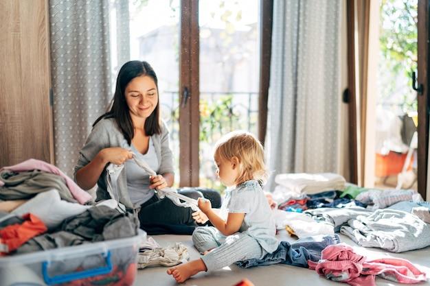 Mamma e figlia stanno piegando i vestiti a casa