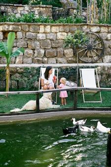 Mamma e figlia sono sedute a un tavolo sul prato vicino allo stagno con le anatre