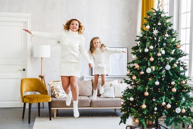 Mamma figlia capelli biondi vestita maglioni leggeri, vacanza in attesa, stanza decorata per festeggiare il natale, divano che salta, divertenti giochi per bambini