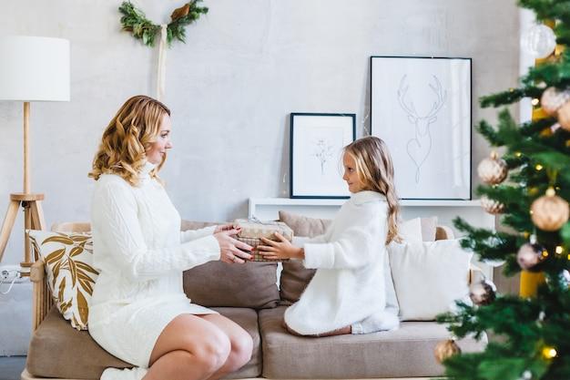 Mamma figlia capelli biondi vestita con maglioni leggeri, vacanza in attesa, stanza decorata festeggia il natale, divano seduto, mamma dà regalo figlia