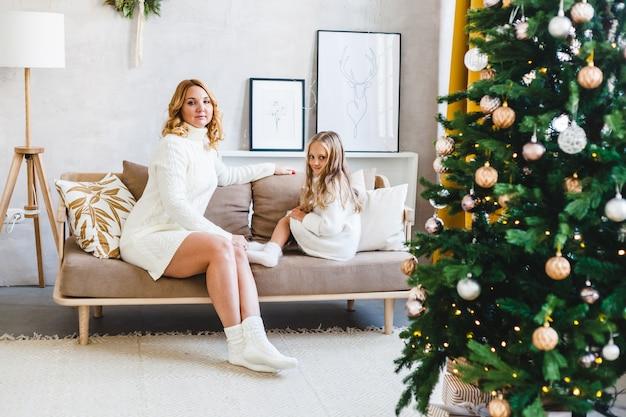 Mamma figlia capelli biondi vestita maglioni leggeri, in attesa delle vacanze, camera decorata festeggiare il natale, seduta sul divano