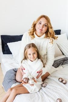 Maglioni bianchi di mamma figlia capelli biondi si trovano a letto con i giocattoli per natale e capodanno