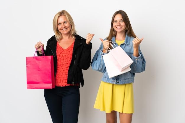 Mamma e figlia che comprano alcuni vestiti isolati sulla parete bianca che dà un pollice in alto gesto con entrambe le mani e sorridente