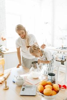 Mamma e figlia che cucinano insieme i biscotti nella cucina