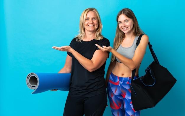 Mamma e figlia che fanno yoga isolato sulla parete blu che estende le mani a lato per invitare a venire