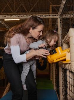 Mamma e figlia sparano con entusiasmo con una pistola giocattolo nel centro di intrattenimento per bambini