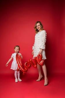 Mamma e figlia in abiti bianchi festivi tengono un palloncino dell'amore su un rosso
