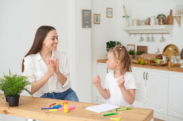 Mamma e figlia hanno finito di fare i compiti, gioiscono e battono le mani. il concetto di prendersi cura di un bambino e aiutare con i compiti.