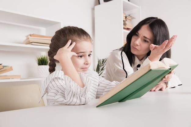 Mamma e figlia che acquisiscono conoscenza insieme seduti a casa.