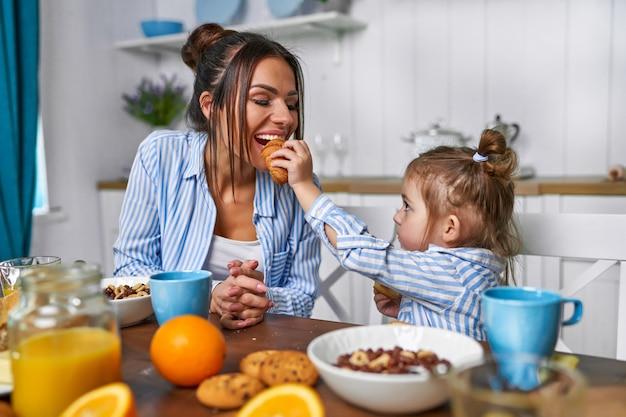 Mamma e figlia la mattina fanno colazione a casa