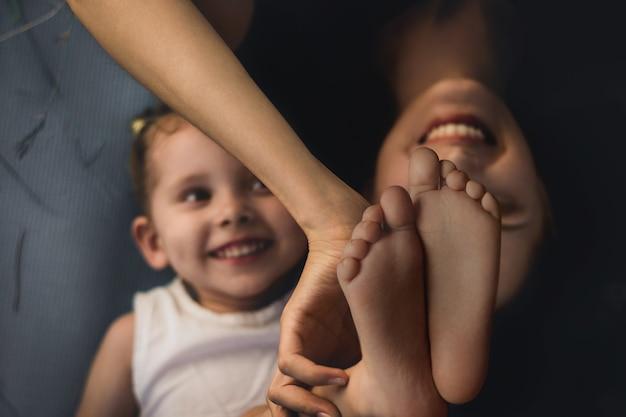 Mamma e figlia si divertono all'aperto. focus sui piedi del bambino in primo piano. messa a fuoco morbida selettiva.