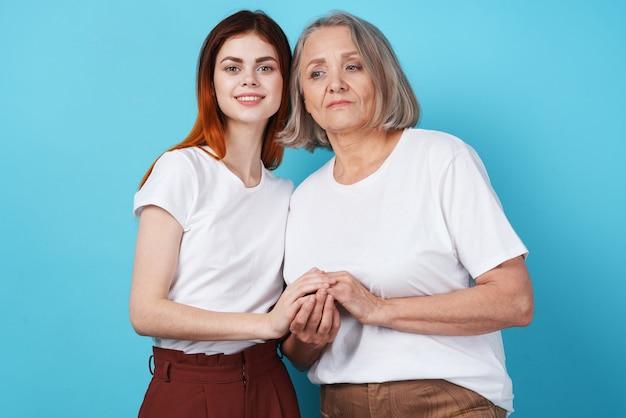 Mamma e figlia si tengono per mano in famiglia di magliette bianche insieme