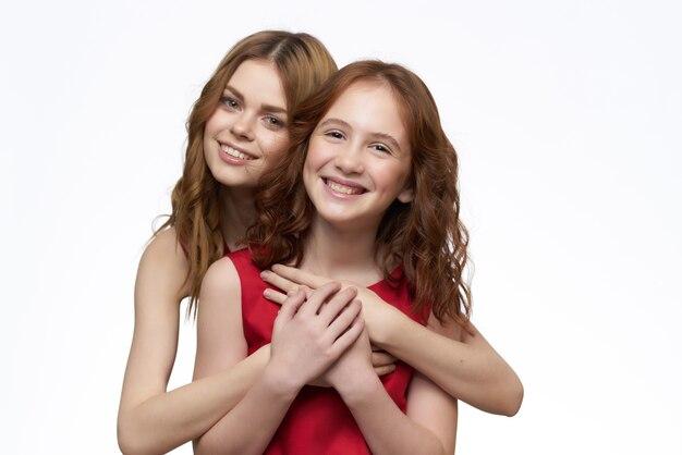 Mamma e figlia si abbracciano con un divertente sfondo chiaro di moda per la famiglia