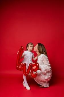 Mamma e figlia abbracciano e tengono in mano un amore di palloncino di alluminio sul rosso