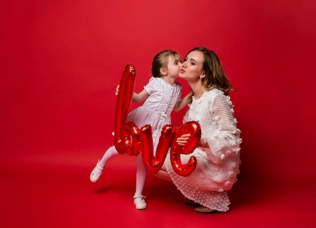 Mamma e figlia si baciano e tengono in mano un amore di palloncino di alluminio sul rosso
