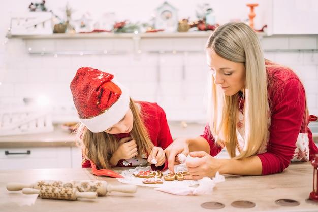 Mamma e figlia in cucina glassano i biscotti di pan di zenzero in maglioni rossi e cappelli di babbo natale con luci