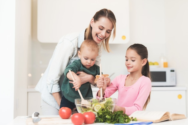 La figlia e il piccolo bambino della mamma preparano un'insalata.