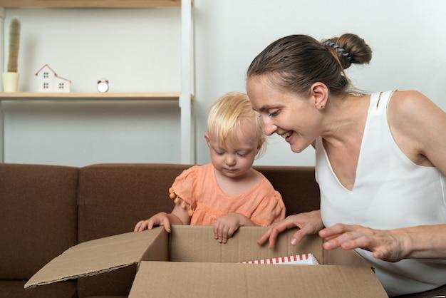 Mamma e figlia guardano in una grande scatola di cartone. pacchetto con regalo.