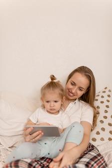 Mamma e figlia guardano lo schermo del telefono