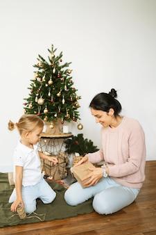 Mamma e figlia che imballano i regali di natale in camera. buon natale e felice anno nuovo concetto. spazio per il testo. momenti intimi in famiglia mattina prima di natale.
