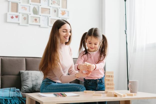 Mamma e figlia giocano un gioco da tavolo in salotto.
