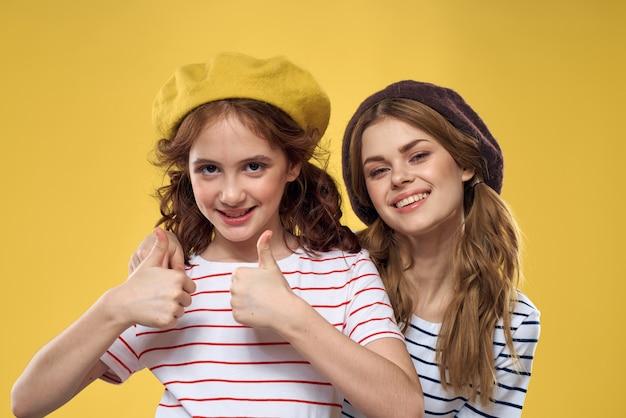 Mamma e figlia in posa si divertono e sorridono, famiglia felice, due sorelle, berretti in testa