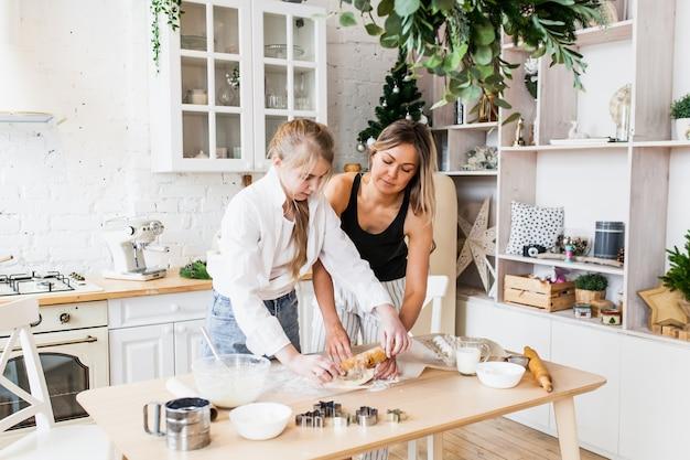 Mamma e figlia preparano biscotti di natale, pasticcini di capodanno, mattarello, stampini, torta